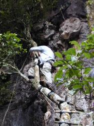 Making the climb to the cave located above the large outcropping.